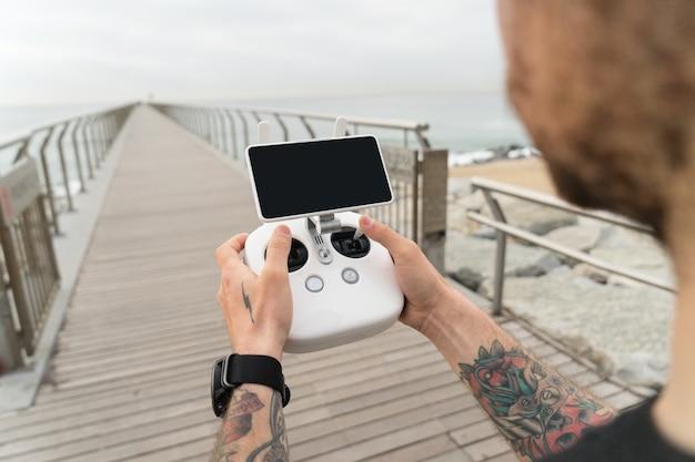 若いプロまたはアマチュアの写真家またはドローンパイロットは、鳥の視点を見るために空中でクワッドコプターを飛ばす準備ができている画面とコントロールを備えたリモートコントロールパネルを持っています。 無料写真