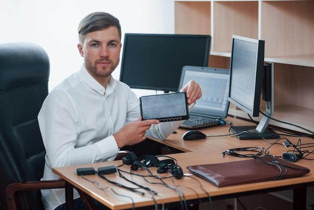 Giovane professionista. l'esaminatore del poligrafo lavora in ufficio con l'attrezzatura della sua macchina della verità Foto Gratuite