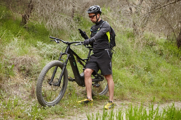 Молодой профессиональный гонщик, одетый в велосипедную одежду и защитное снаряжение, ищет gps-координаты с помощью навигатора на своем смартфоне, катаясь на велосипеде на батарейках в лесу в солнечный день Бесплатные Фотографии