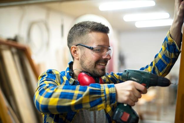 Falegname giovane lavoratore professionista con occhiali protettivi che tiene trapano e lavora al suo progetto in officina Foto Gratuite