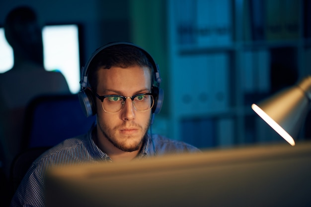 Young programmer in eyewear and headphones working in office Free Photo