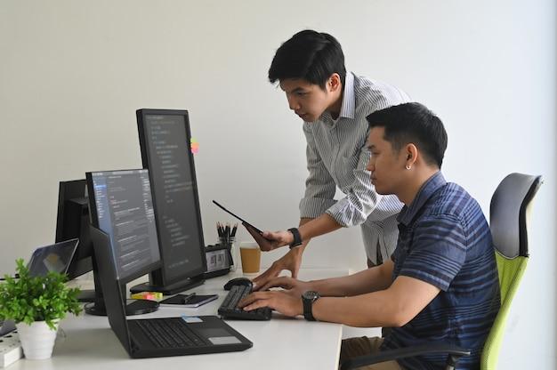 Молодые программисты, работающие на компьютере и планшете в современном офисе на рабочем месте. Premium Фотографии