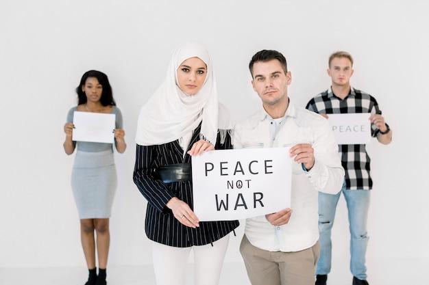若い抗議者、イスラム教徒の女性、白人男性、平和を救うことを唱え、戦争スローガンのないポスター Premium写真