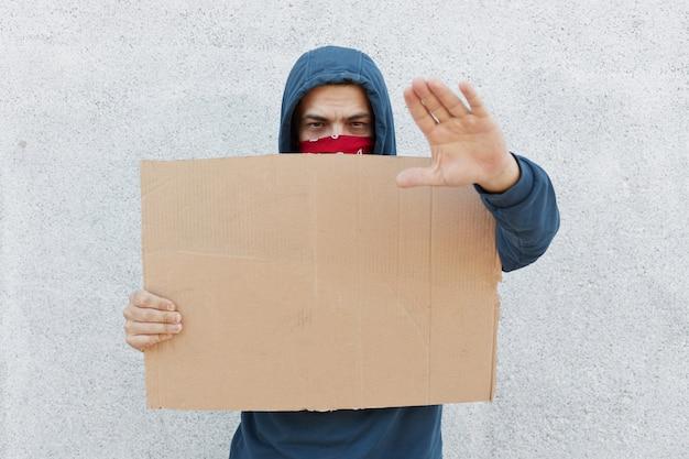 Il giovane uomo di protesta in cappuccio e che copre il suo fronte di bandana sta contro il muro bianco che tiene cartone Foto Gratuite