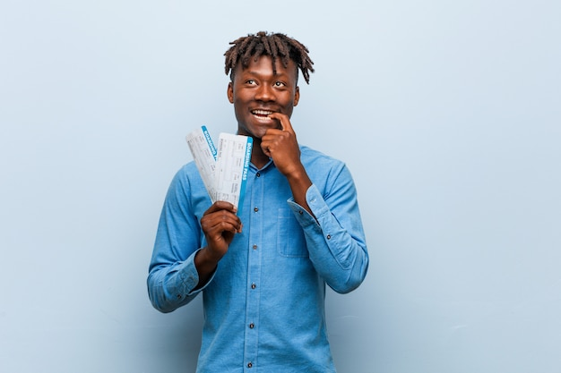 Young rasta black man holding an air tickets relaxed thinking about something looking at a copy space. Premium Photo