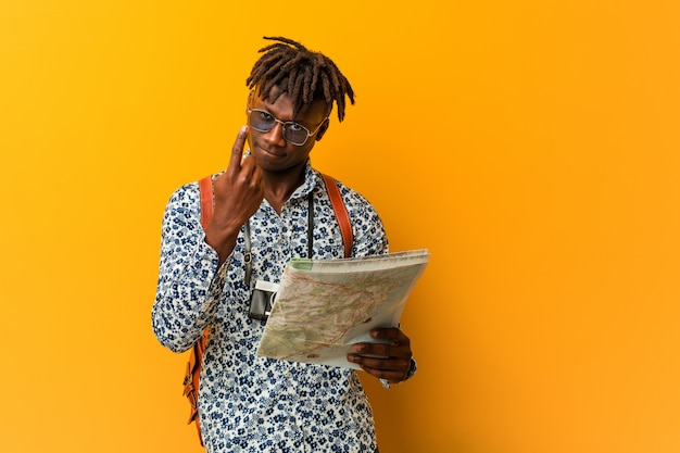 Young rasta black man holding a map pointing with finger at you as if inviting come closer. Premium Photo