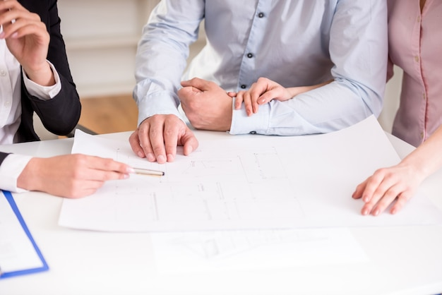 Young realtor showing contract with apartment to couple. Premium Photo