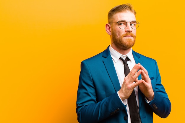 Young red head businessman scheming and conspiring, thinking devious tricks and cheats, cunning and betraying against orange Premium Photo