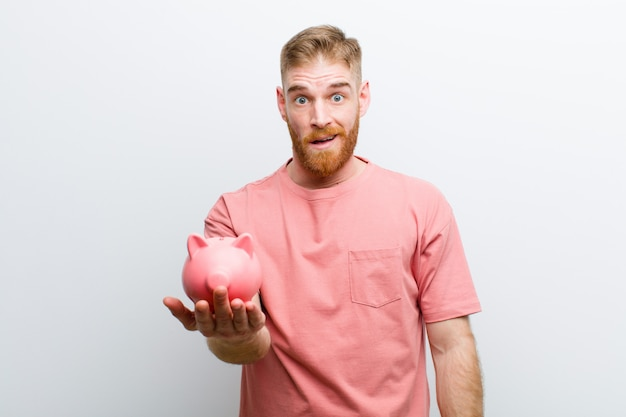 Young red head man holding a piggy bank  white Premium Photo