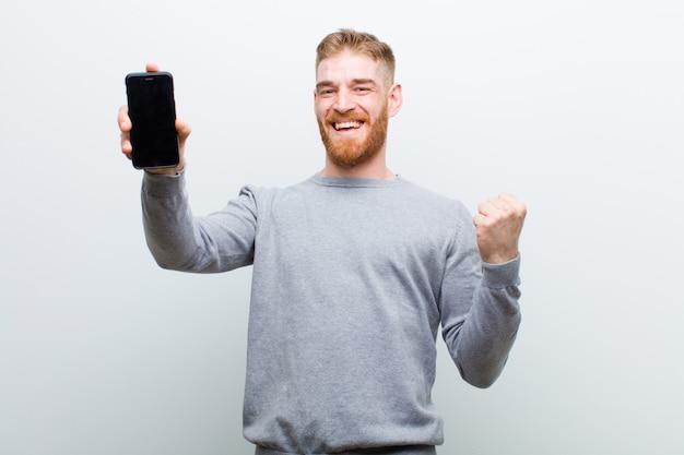 Молодой рыжий мужчина со смартфоном на белом фоне Premium Фотографии