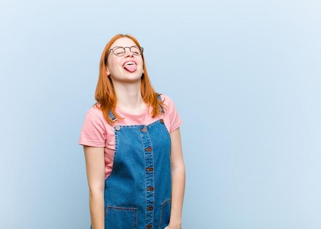 陽気な、屈託のない、反抗的な態度、冗談と舌を突き出し、楽しんで若い赤い頭のきれいな女性 Premium写真