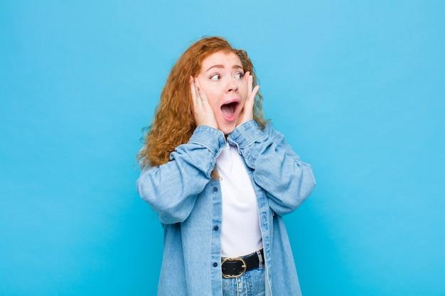 Молодая рыжая женщина чувствует себя счастливой, взволнованной и удивленной, глядя в сторону, положив руки на лицо на синей стене Premium Фотографии