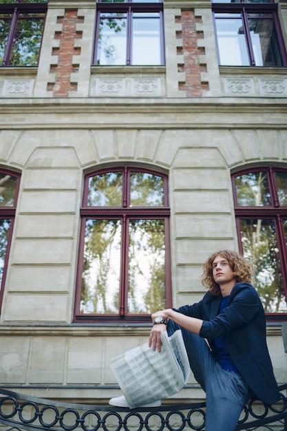Молодой красноватый человек читает газету возле здания в старом стиле Бесплатные Фотографии