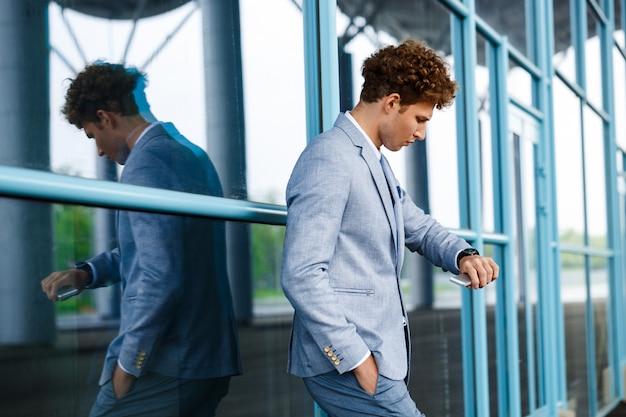 Giovane uomo d'affari dai capelli rossi che osserva sulla vigilanza Foto Gratuite