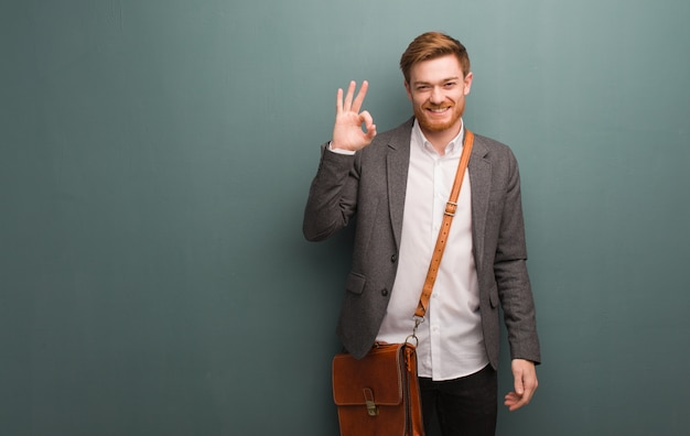 Young redhead business man cheerful and confident doing ok gesture Premium Photo