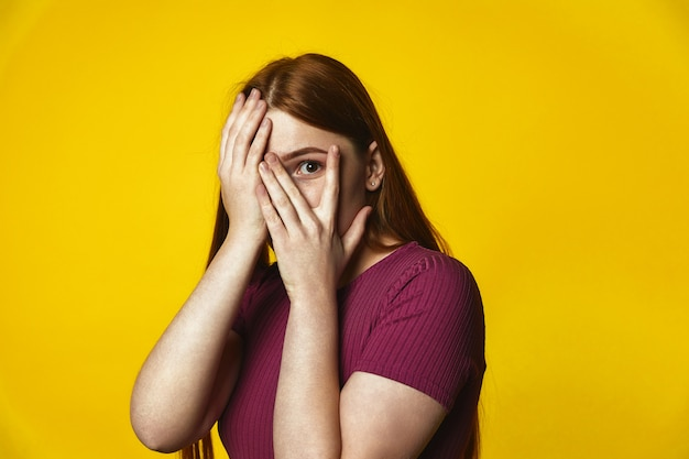 Young redhead caucasian girl is covering face with hands and looking through the fingers Free Photo
