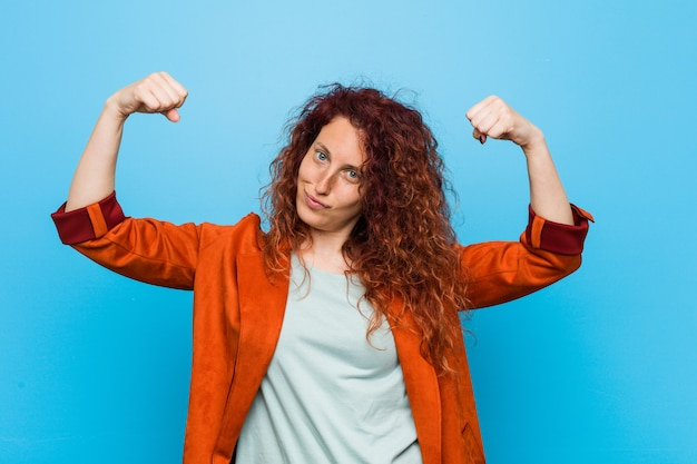 Young redhead elegant woman showing strength gesture with arms, symbol of feminine power Premium Photo