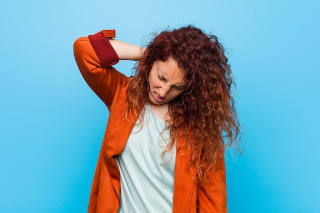 Young redhead elegant woman suffering neck pain due to sedentary lifestyle. Premium Photo