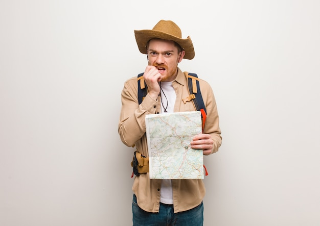 Young redhead explorer man biting nails, nervous and very anxious. holding a map. Premium Photo