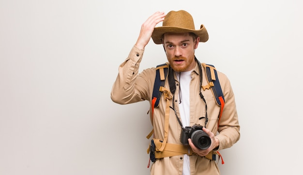 Young redhead explorer man worried and overwhelmed. holding a photo camera. Premium Photo
