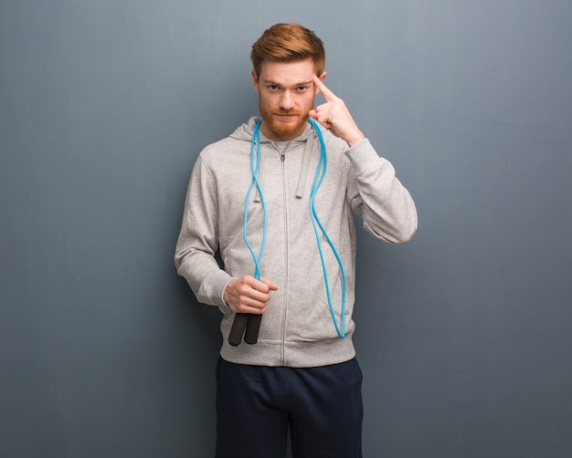 Young redhead fitness man thinking about an idea. he is holding a jump rope. Premium Photo