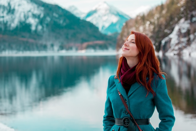 Young redhead girl in coat near lake in alps, germany Premium Photo