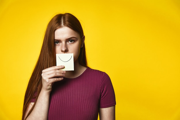 Young redhead girl has serious look and keeps a card with smile on her mouth Free Photo