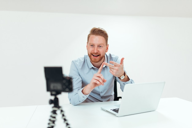 Young redhead man recording video for his vlog in bright space. Premium Photo