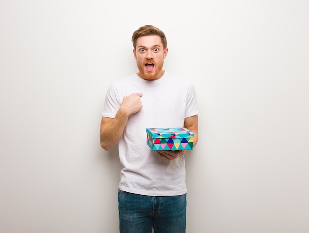 Young redhead man surprised, feels successful and prosperous. holding a gift box. Premium Photo