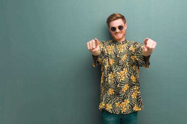 Young redhead man wearing exotic summer clothes cheerful and smiling pointing to front Premium Photo