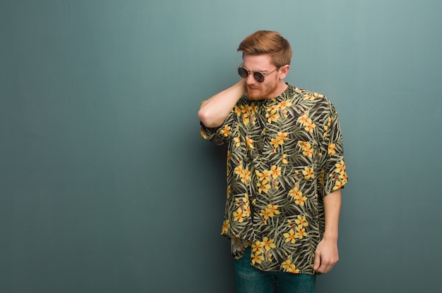 Young redhead man wearing exotic summer clothes suffering neck pain Premium Photo