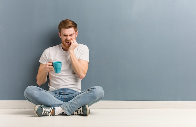 Young redhead student man sitting on the floor biting nails, nervous and very anxious Premium Photo