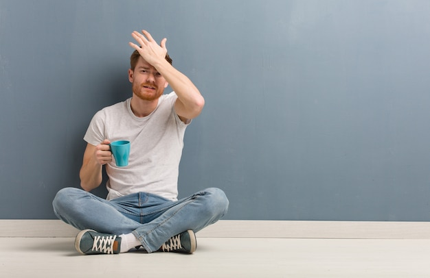 Young redhead student man sitting on the floor worried and overwhelmed. he is holding a coffee mug. Premium Photo