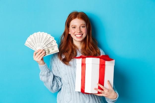 크리스마스 선물 상자와 돈을 들고 젊은 빨간 머리 여자 기쁘게 웃 고, 파란색 배경 위에 서. 프리미엄 사진
