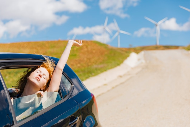Young redhead woman loving life out of car window Free Photo
