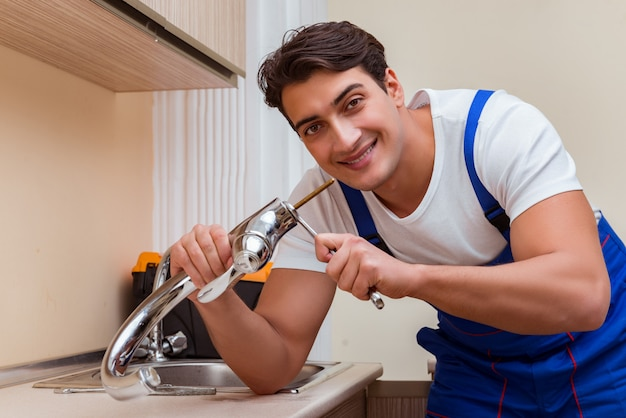 Young repairman working at the kitchen Premium Photo