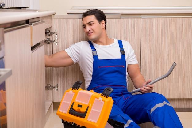 Young repairman working at the kitchen Premium Photo