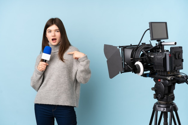 Young reporter woman holding a microphone and reporting news with surprise facial expression Premium Photo