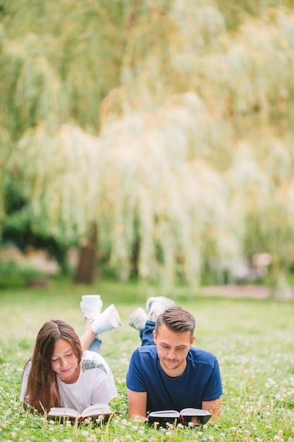 公園で横になっていると、本を読んでロマンチックなカップル Premium写真