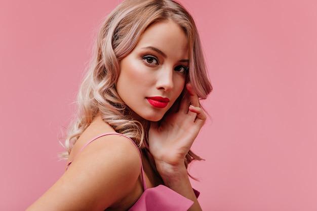 Giovane donna bionda carina romantica di aspetto modello con trucco luminoso in posa per il ritratto sulla parete isolata rosa Foto Gratuite