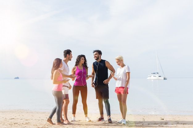 Young runners group on beach talking hold mobile phones Premium Photo