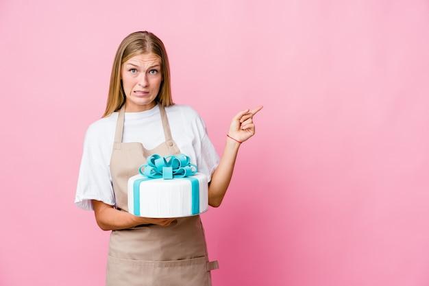 맛있는 케이크를 들고 젊은 러시아 베이커 여자 복사 공간에 검지 손가락으로 가리키는 충격 프리미엄 사진