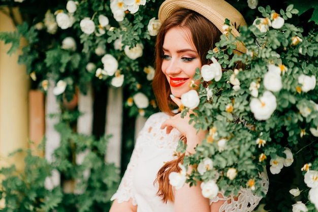 Young russian beauty. attractive girl in vintage top and curly red hair and straw hat posing for camera with fence and green trees Premium Photo