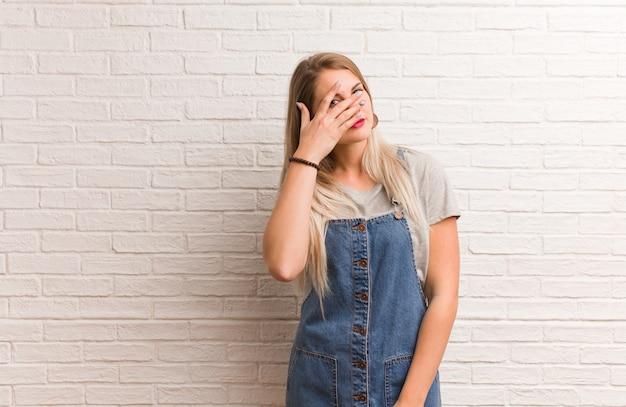 恥ずかしいと同時に笑っている若いロシアの流行に敏感な女性 Premium写真