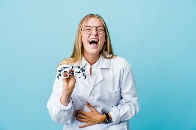 Молодая русская женщина-оптометрист на синем счастливо смеется и веселится, держа руки на животе. Premium Фотографии