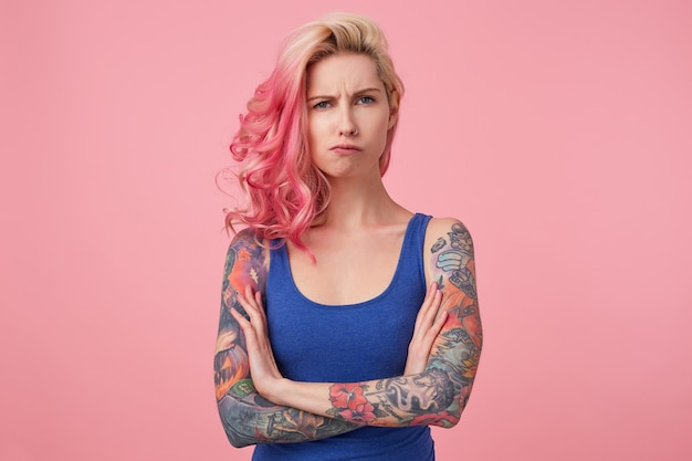 Young sad frowning beauty woman with pink hair, stands with crossed arms, looks displeased, wears a blue shirt. people and emotion concept. Free Photo