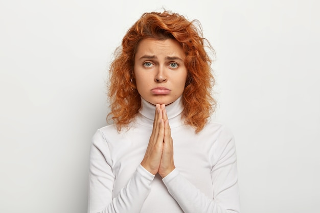 Young sad girl asks for something, keeps hands in praying gesture, pleads for help, purses lower lip, looks with miserable face expression , has foxy curly hair, healthy skin. i am so sorry Free Photo