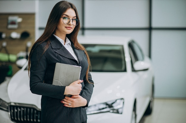 Young sales woman at carshowroom standing by the car Free Photo