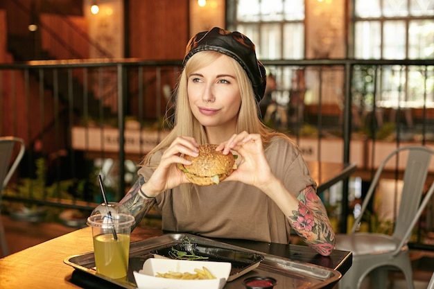 Young satisfied blonde long haired lady with tattooes posing over modern cafe interior and holding hamburger in hands, looking aside and smiling happily, wearing trendy clothes Free Photo
