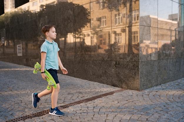 ペニーボードを手に歩いて明るい服を着た若い学校のクールな男の子 無料写真